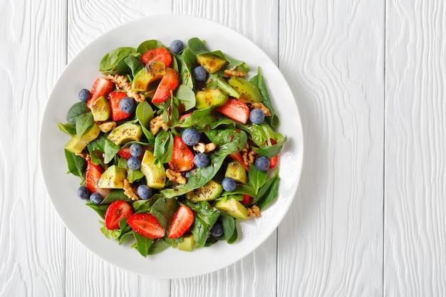 Salada de espinafre, abacate, nozes e frutas vermelhas com vinagre balsâmico e molho de sementes de papoula em um prato branco