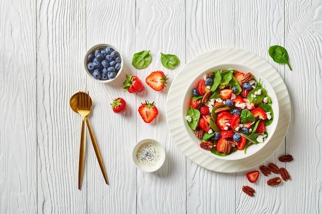 Salada de espinafre e morango com noz-pecã e queijo feta esfarelado em uma tigela branca sobre uma mesa de madeira com molho de sementes de papoula, vista horizontal de cima, camada plana, espaço livre