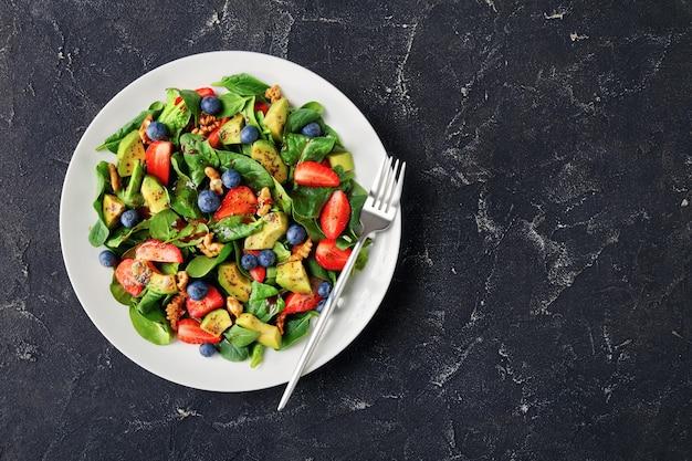 Salada de espinafre fresco, nozes, abacate, morango e mirtilo, servida em um prato branco sobre uma mesa de concreto