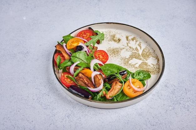 Salada de estilo caseiro com berinjela frita, tomate, rúcula, espinafre, alface e molho em um prato de cerâmica