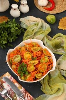 Salada de estilo coreano com tomates verdes e cenouras em uma saladeira branca em uma foto escura e vertical