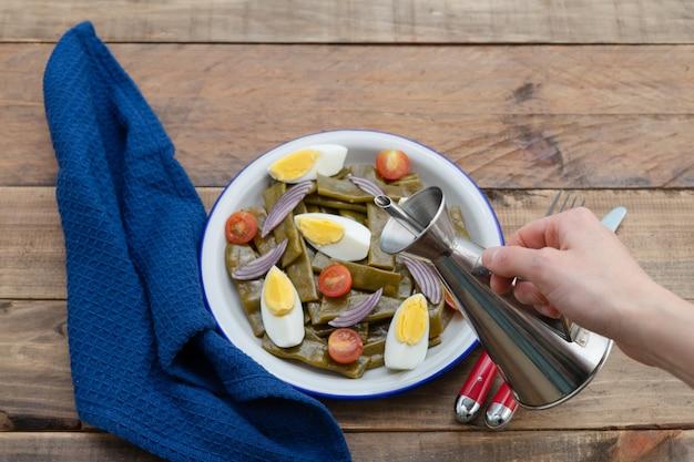Salada de feijão verde com ovo cozido e tomate. mão de uma mulher com lata de óleo. copie o espaço. fundo de madeira.