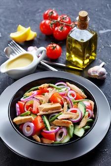 Salada de feijão verde e atum rápida e fácil com vegetais: tomate, pepino, cebola roxa em um fundo escuro de concreto