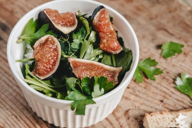 Salada de figos frescos e ervas em uma tigela branca sobre um fundo de madeira. uma salada verde saudável feita com frutas e vegetais frescos. nutrição apropriada. corte os figos em pedaços. estética alimentar