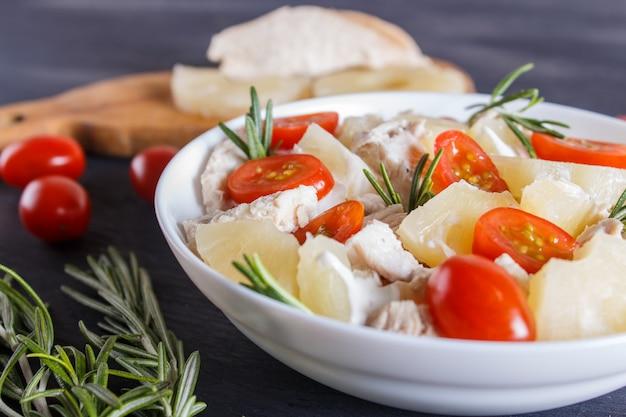 Salada de filé de frango com alecrim, abacaxi e tomate cereja em madeira azul escuro