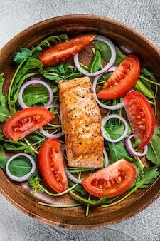Salada de filé de salmão com folhas verdes de rúcula, abacate e tomate em prato de madeira