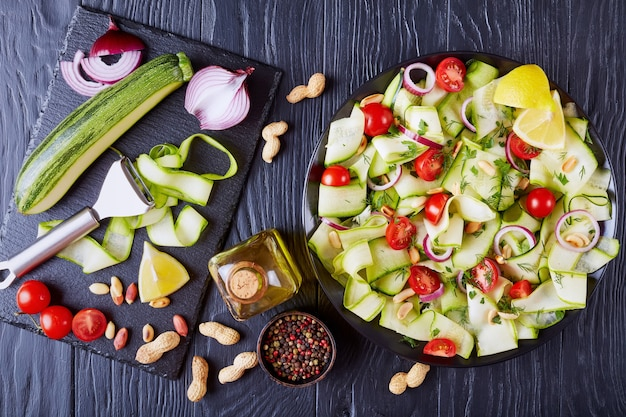 Salada de fita de abobrinha de verão com tomate, amendoim torrado, cebola roxa e verduras em uma placa preta em uma mesa de madeira com ingredientes em uma placa de ardósia, cozinha italiana, vista de cima, close-up