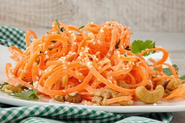 Salada de fita de cenoura banhada com molho de iogurte temperada com nozes fritas e sementes de gergelim