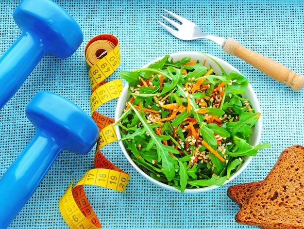 Salada de fitness deliciosa e nutritiva com cenoura rúcula e gergelim. o conceito de perda de peso e estilo de vida esportivo