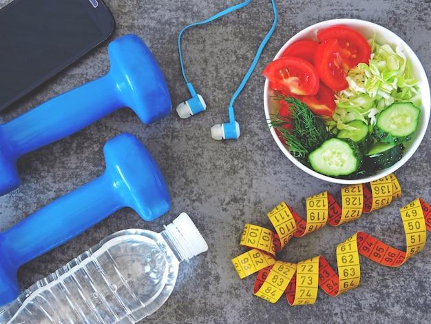Salada de fitness, halteres e fita métrica