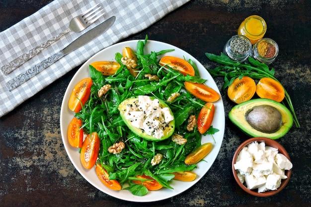 Salada de fitness saudável com rúcula, abacate, queijo feta e tomate cereja amarelo.