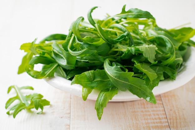 Salada de folhas de rúcula fresca crua em prato de cerâmica branca com fundo de madeira claro