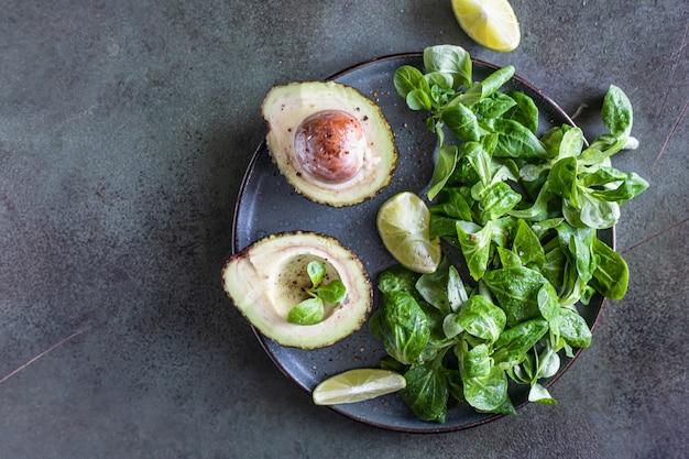 Salada de folhas verdes de abacate e fatias de limão gorduras saudáveis vista superior copiar espaço