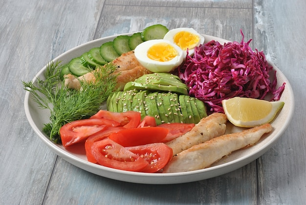 Salada de frango com abacate, tomate, couve roxa, pepino, ovos cozidos e salsa. tigela de almoço saudável com legumes e frango no fundo de madeira