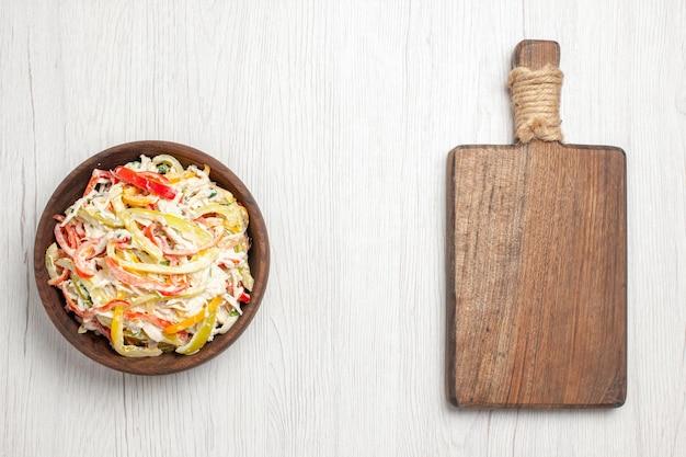 Salada de frango com mayyonaise e vegetais fatiados dentro do prato na mesa branca e clara salada de carne fresca