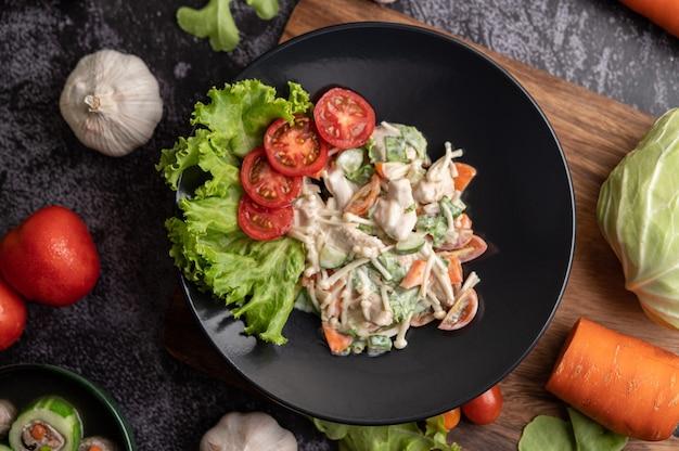 Salada de frango com tomate, cogumelo agulha, cenoura, alface e pepino em um prato preto