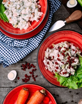 Salada de frango e salada de legumes com maionese em cima da mesa
