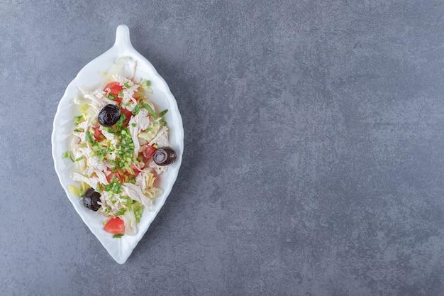 Salada de frango em cubos no prato em forma de folha.