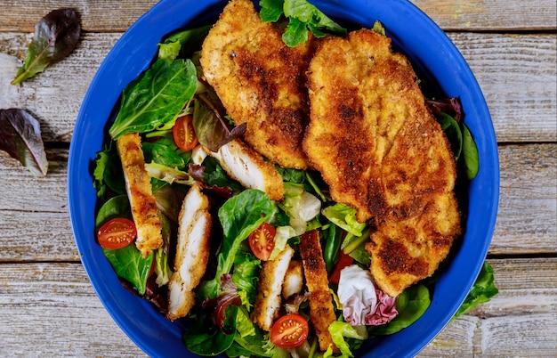 Salada de frango grelhado com legumes frescos na mesa de madeira velha