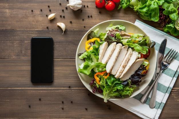 Salada de frango saudável ao lado de smartphone no fundo da mesa de madeira