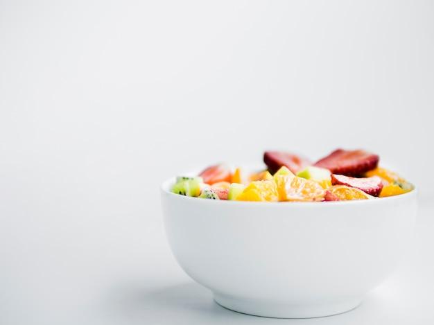 Salada de fruta fresca saborosa em tigela sobre fundo branco