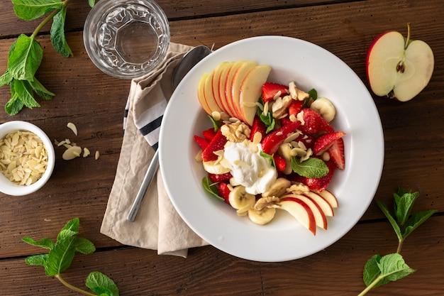 Salada de fruta misturada em uma opinião superior do backgroun de madeira. prato de comida saudável