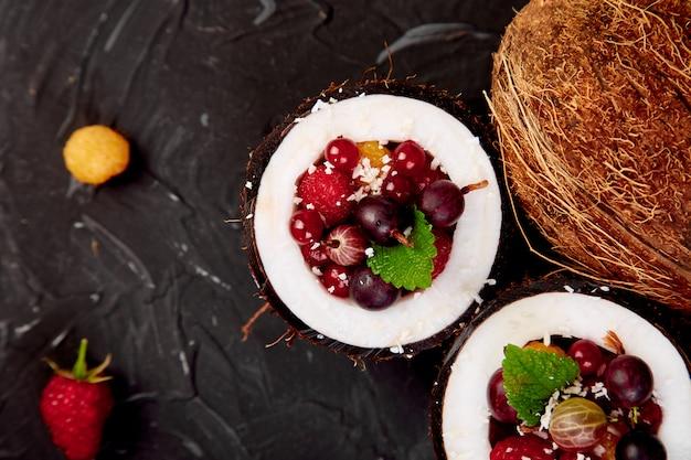 Salada de frutas agrus, groselha, rasbberry em tigela de casca de coco