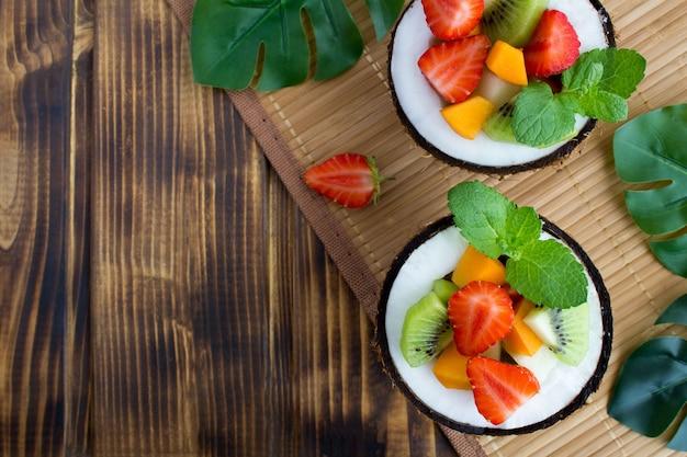 Salada de frutas ao meio coco na mesa tropical. vista superior. copie o espaço.