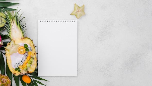 Salada de frutas ao meio de abacaxi com o bloco de notas vazio