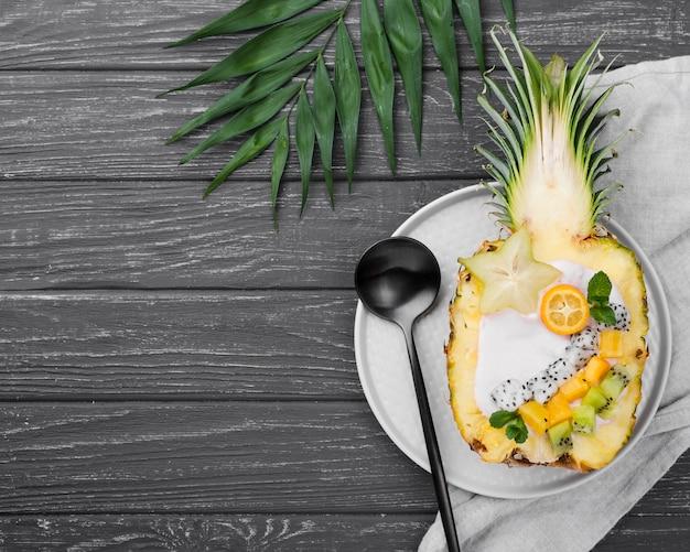 Salada de frutas ao meio de abacaxi e colher preta