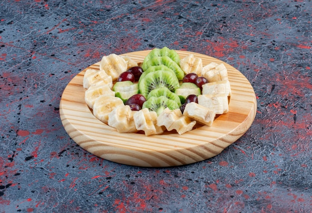 Salada de frutas com fatias de banana, kiwies e frutas vermelhas em uma placa de madeira.