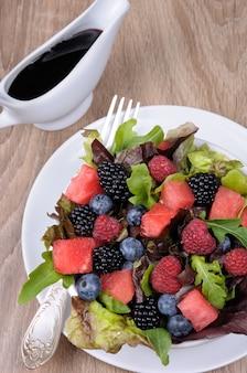 Salada de frutas com fatias de melancia de amora-preta framboesa mirtilo e mistura de folhas verdes