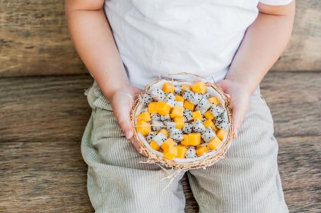 Salada de frutas com fruta do dragão e mamão ao meio coco na mão