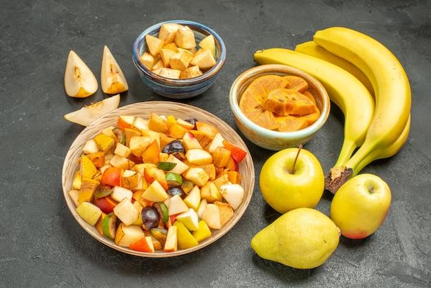 Salada de frutas com frutas frescas fatiadas em uma mesa cinza-escuro com frutas frescas