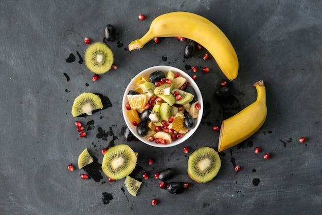 Salada de frutas com frutas maduras exóticas tropicais picadas em cubos, laranja, kiwi, banana, uvas, romãs