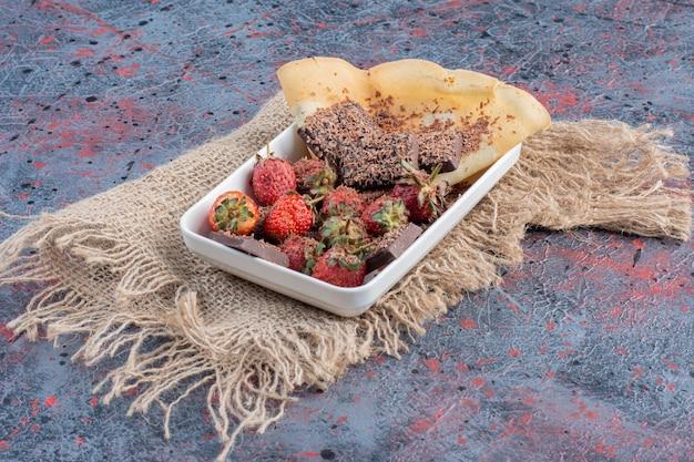 Salada de frutas com frutas vermelhas e chocolate amargo.