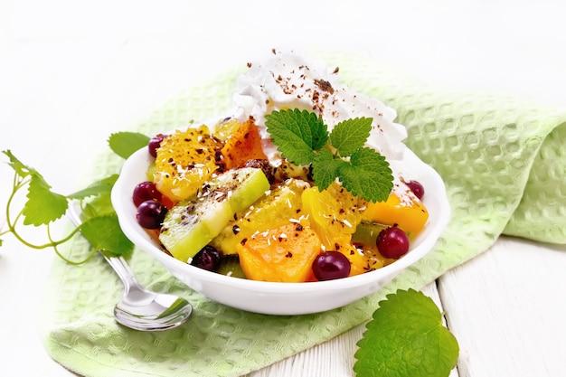 Salada de frutas com laranja, kiwi, cranberries e abóbora assada, chantilly, polvilhada com chocolate e coco com hortelã em uma tigela sobre uma toalha no fundo da placa de madeira