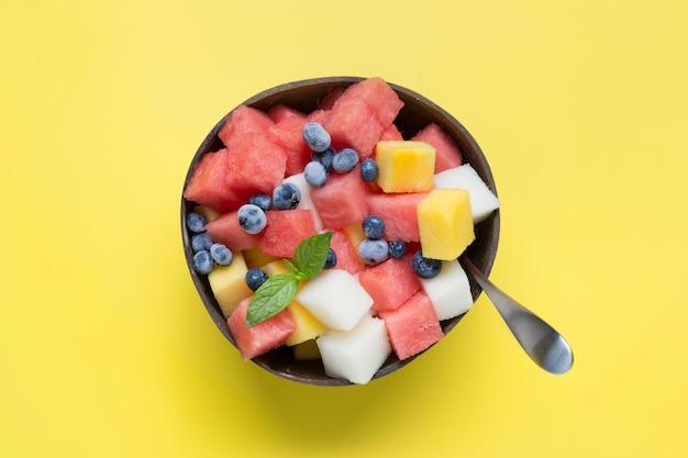 Salada de frutas de melancia, melão e manga em uma tigela de coco em amarelo
