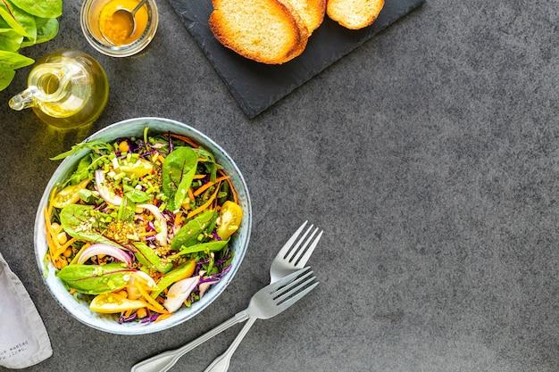 Salada de frutas e vegetais frescos em um prato na superfície de pedra preta