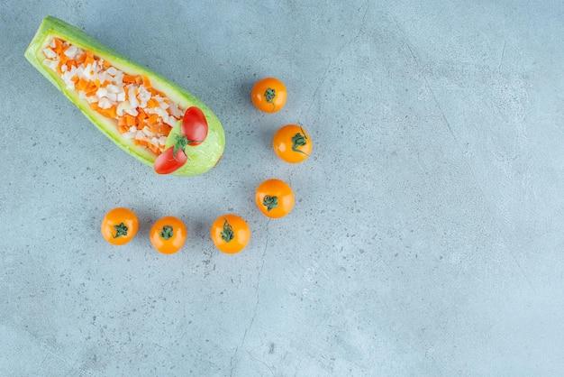 Salada de frutas e vegetais picada dentro de uma abobrinha entalhada.