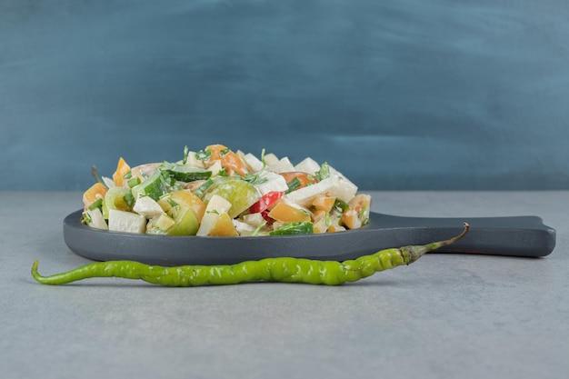 Salada de frutas e vegetais picada em uma placa de madeira.
