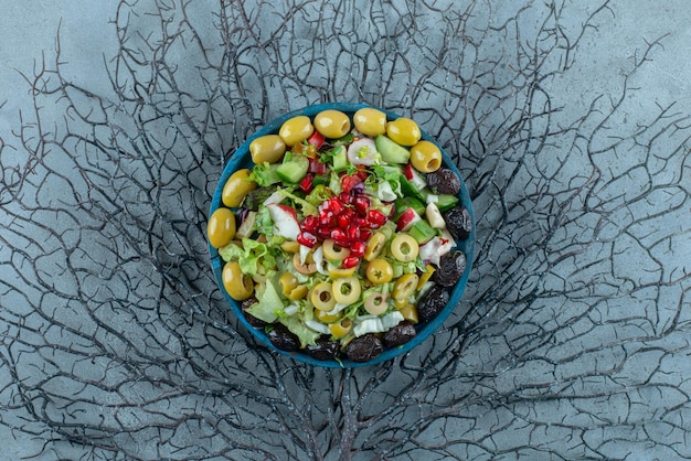 Salada de frutas e vegetais picada em uma travessa.