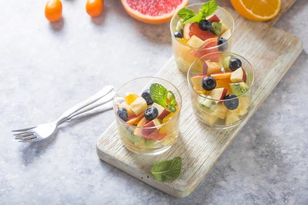 Salada de frutas em copos, alimentos frescos de verão, coco de abacaxi saudável blueberries laranja orgânico kiwi. vista do topo