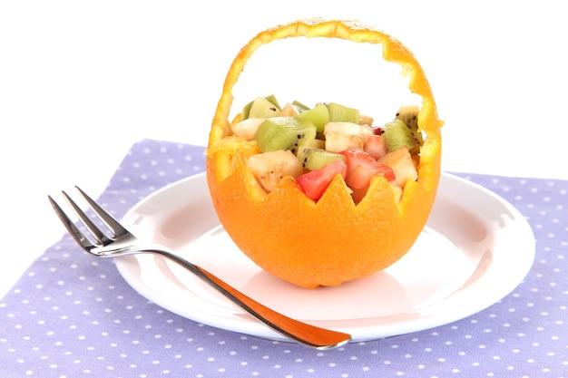Salada de frutas em laranja oca isolada no branco