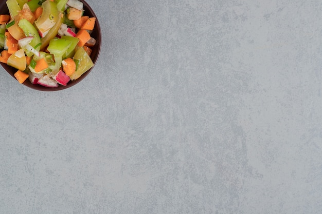 Salada de frutas em um copo de madeira sobre uma superfície de concreto