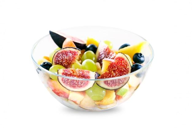 Salada de frutas em uma tigela de vidro isolado no fundo branco com sombra
