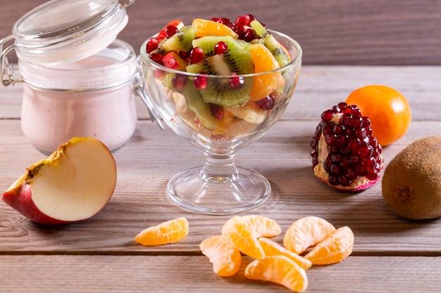 Salada de frutas em uma tigela transparente e várias frutas alimentos saudáveis, ricos em vitaminas e antioxidantes