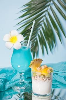 Salada de frutas exóticas tropicais com cereais e iogurte em um copo com cocktail azul.