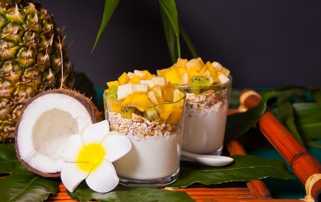 Salada de frutas exóticas tropicais com cereais e iogurte em um copo na folha de palmeira.