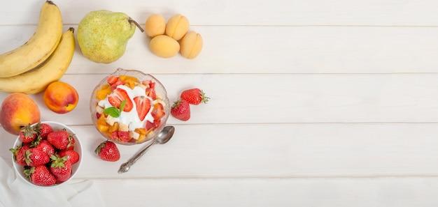 Salada de frutas frescas com iogurte em uma tigela com espaço de cópia. pequeno-almoço saudável de fitness.